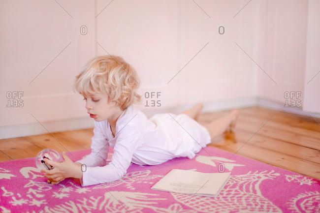 Four year old boy lying on rug gazing at snow globe