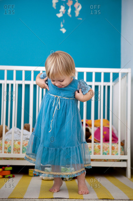 Female toddler admiring her party dress in bedroom