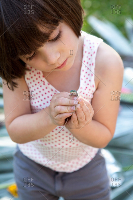 Girl holding and looking at green anole lizard in garden