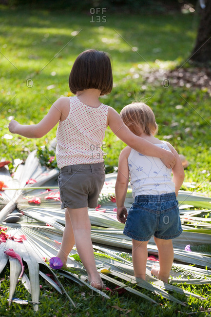 Girl with arm around toddler sister with flower and leaf display in garden
