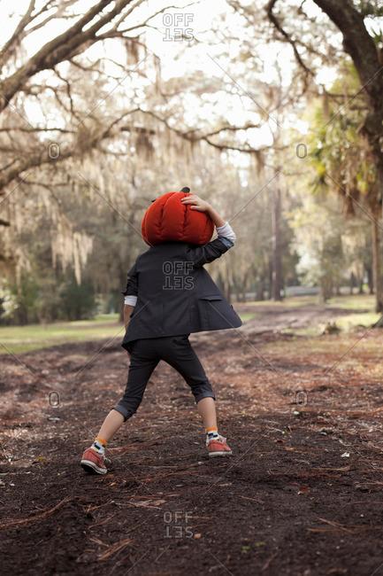 Boy running in forest holding onto pumpkin head