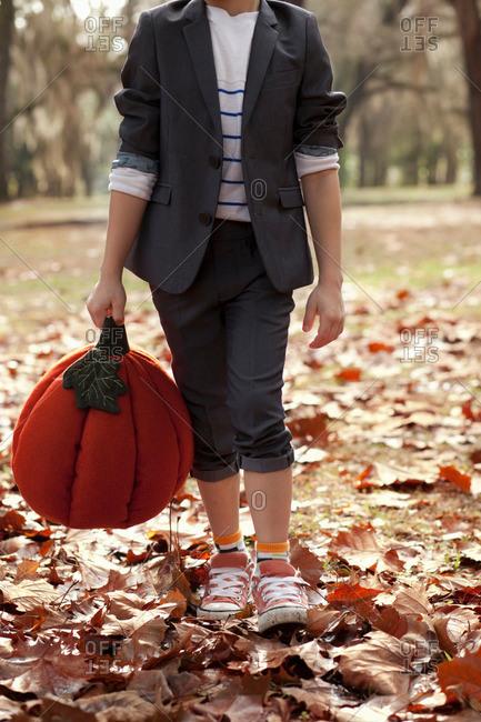 Boy in forest holding pumpkin head