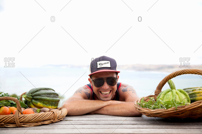 Portrait of mid adult man in baseball cap and shades leaning forward on picnic bench