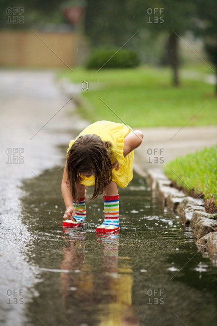 Girl wearing rubber boots picking leaf from rain puddle