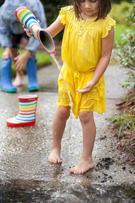 Girl pouring water from rubber boots into rain puddle