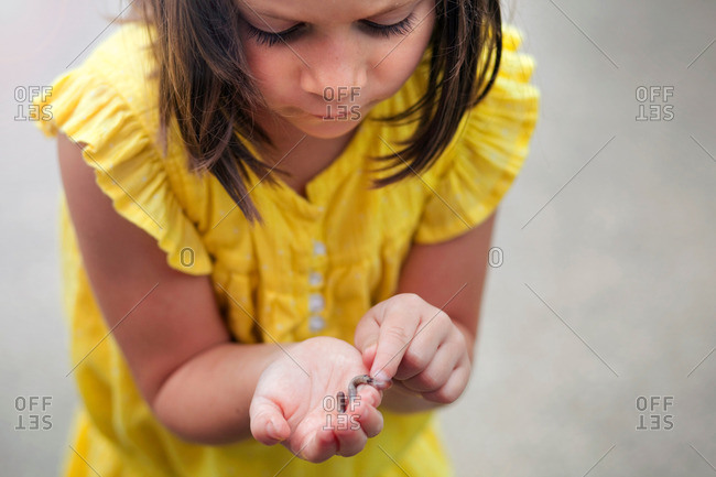 Girl holding and looking down at worm