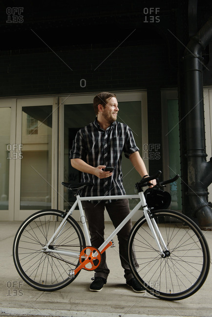 Male cycle messenger checking directions on smartphone outside office