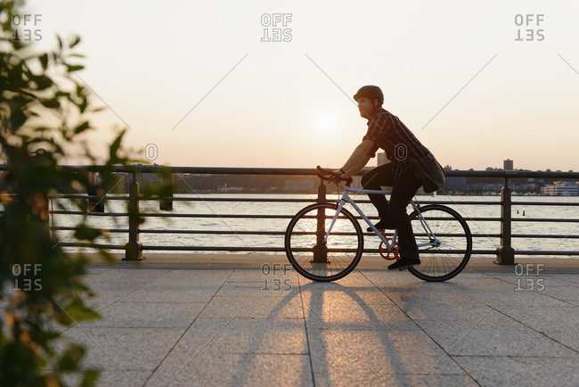 Male messenger cycling along city riverside