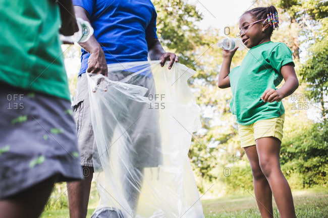 Father picking up litter with son and daughter at eco camp