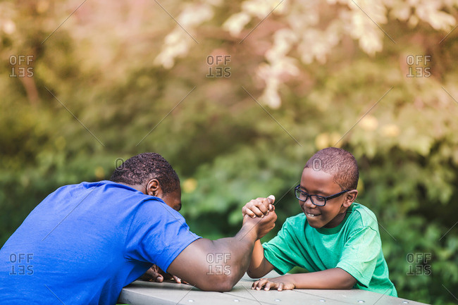 Father arm wrestling with son at parkland eco camp