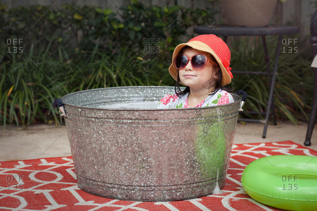 Portrait of girl wearing sunhat and sunglasses sitting in bubble bath in garden