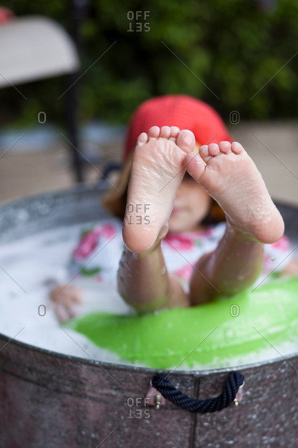 Girl sitting in bubble bath in garden with feet sticking out