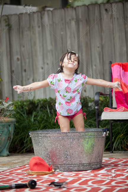 Girl standing in bathtub in garden with arms outstretched