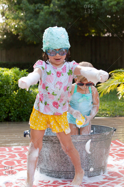 Girl and toddler sister playing in bubble bath in garden