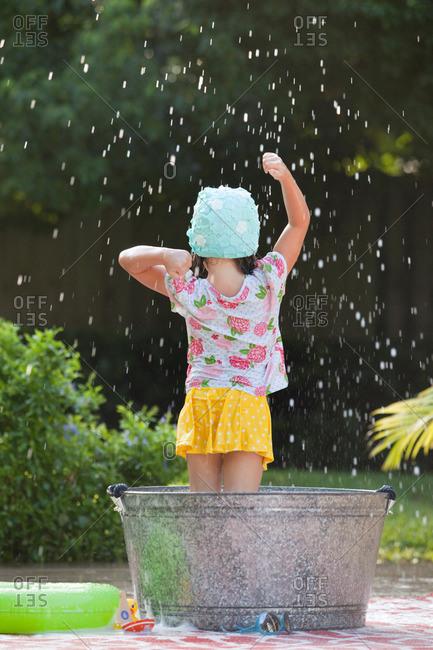 Rear view of girl standing in bubble bath in garden splashing soap bubbles
