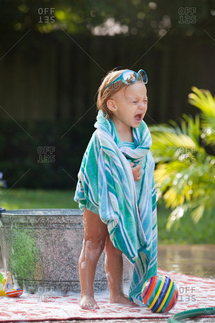 Female toddler wrapped in towel crying beside bubble bath in garden