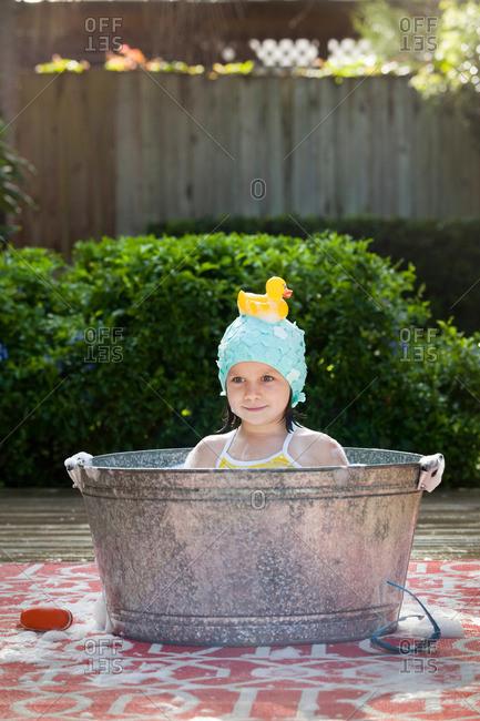 Portrait of girl in bubble bath in garden with rubber duck on head