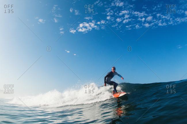 Mid adult man surfing wave, Leucadia, California, USA