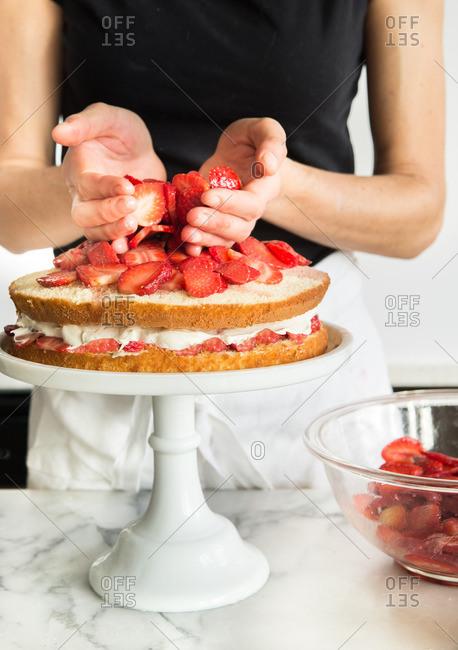 Woman preparing strawberry and whipped cream layer cake
