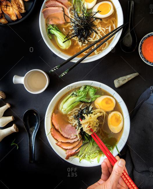 Person heating bowl of ramen with chopsticks