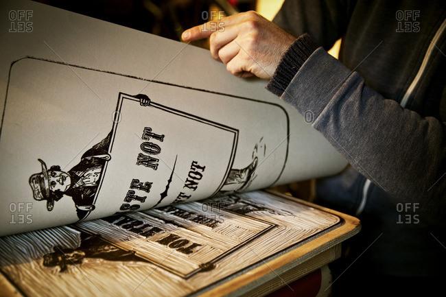 A signwriter lifting a sheet of imprinted card off a cutout linoneum surface