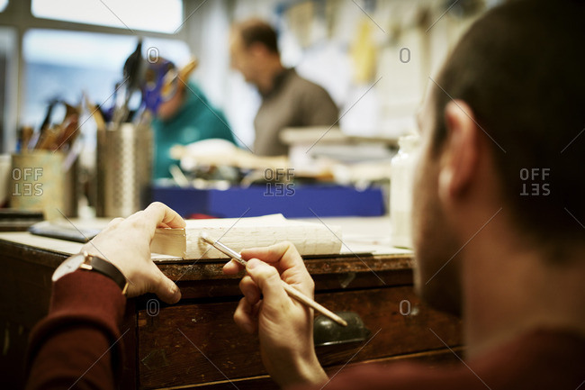 A man working on the bound pages of a book with a hand tool to apply glue