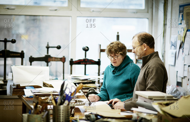 Two people working in a book binding business Surrounded by tools and book presses