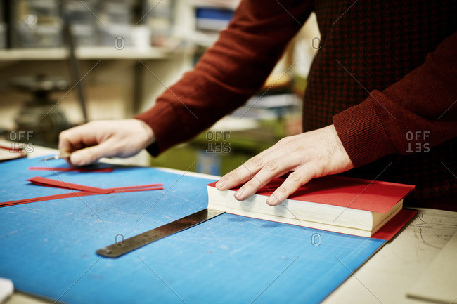A man working on a bench measuring and cutting the material for recovering a book, in a bookbinding workshop
