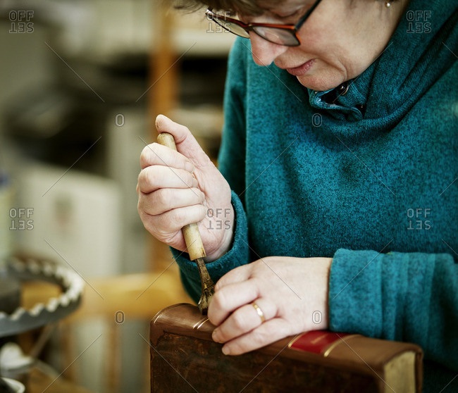 A woman working on the spine of a bound book with a hand tool
