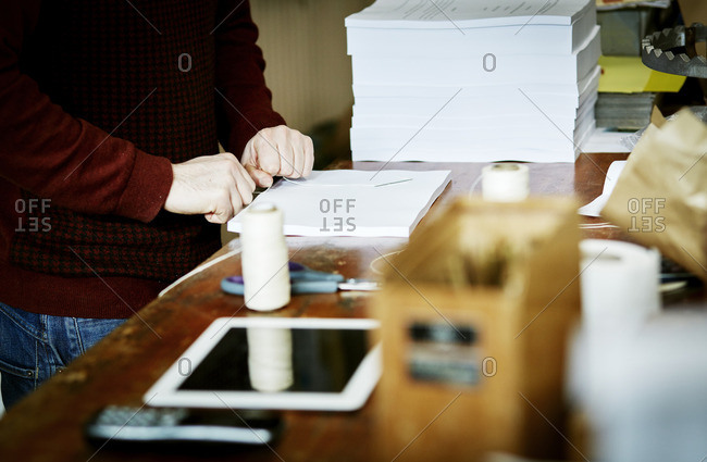 A digital tablet on a workbench, and a man handstitching a pile of paper pages binding them