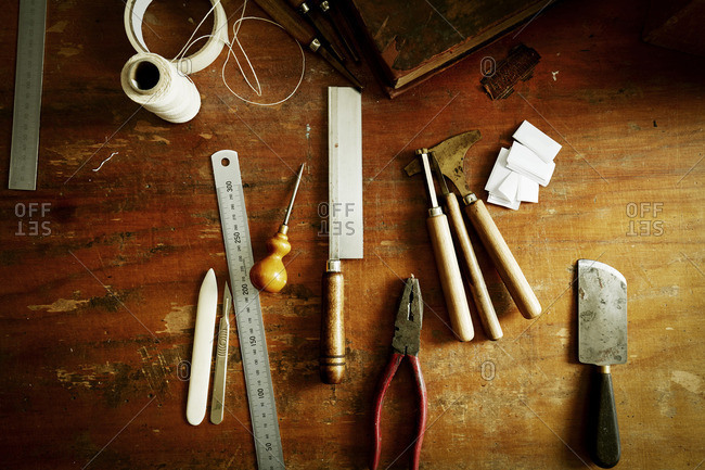 Overhead view of a workbench with hand tools for bookbinding
