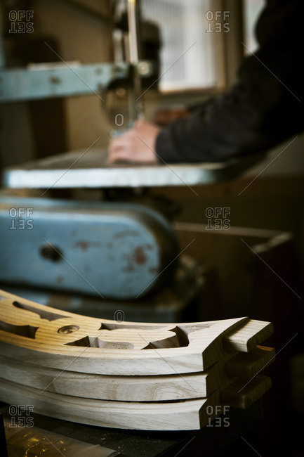 A man working in a furniture maker's workshop using a mechanical saw Wooden chair backs stacked on  a workbench