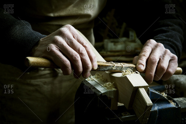 A man working in a furniture maker's workshop, using a rasp on a piece of wood in a clamp