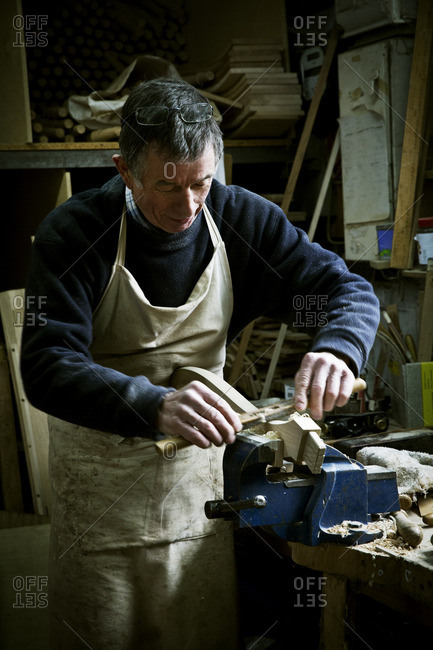 A man working in a furniture maker's workshop, sanding a piece of wood held in a clamp
