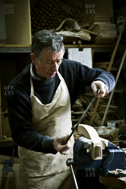 A man working in a furniture maker's workshop using a rasp on a wooden shape in a clamp