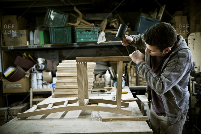 A man working in a furniture maker's workshop assembling a chair