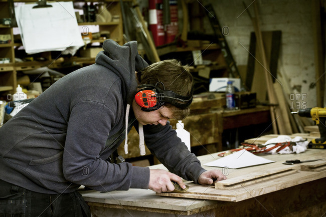 A man working in a furniture maker's workshop wearing ear defenders and using a sharp chisel on wood