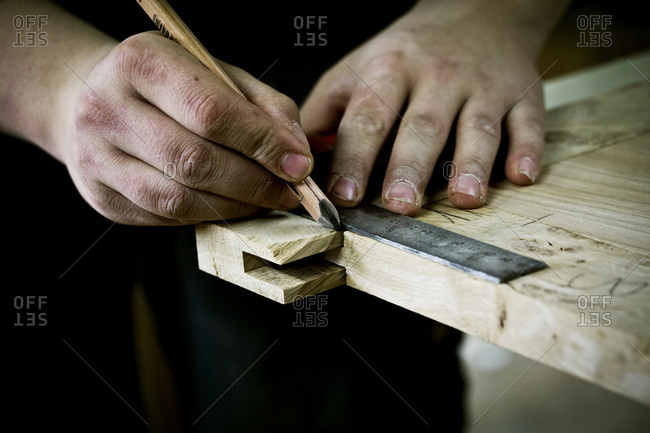 A man working on wood, measuring a joint or corner with a ruler and pencil
