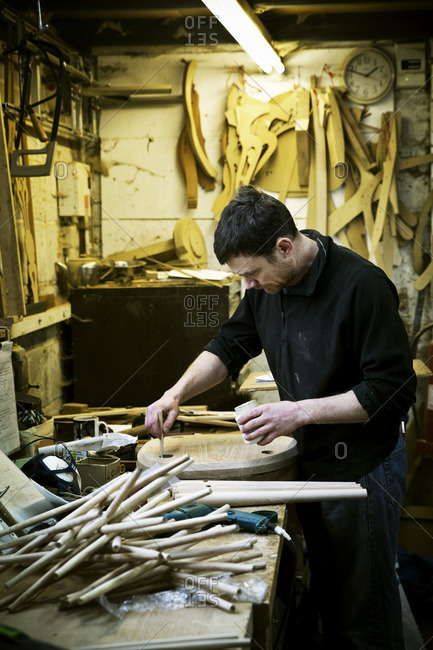 A man working in a furniture maker's workshop Chairlegs on the bench