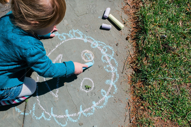 Child sitting on pavement drawing with chalk
