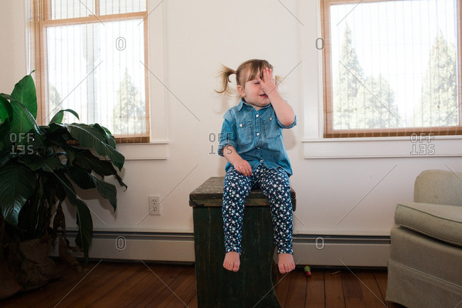Toddler girl sitting on a side table