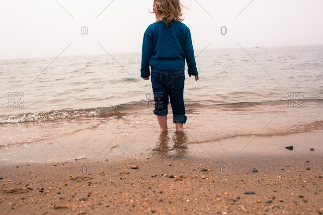 Toddler girl in jeans playing on beach