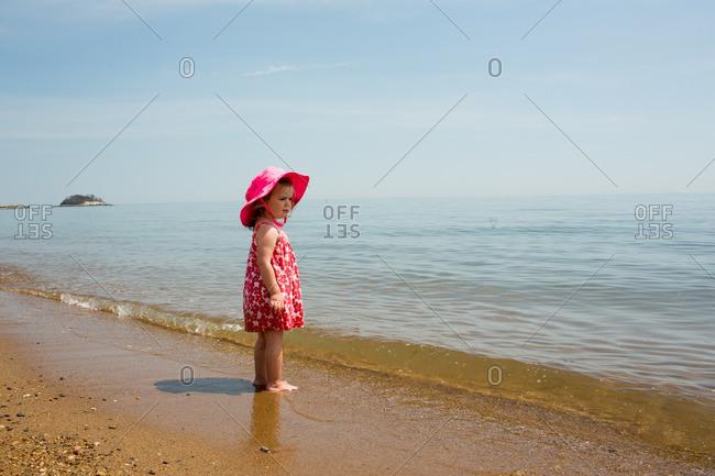 Toddler girl playing on sandy beach