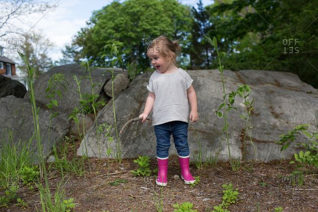 Toddler standing by tall plants