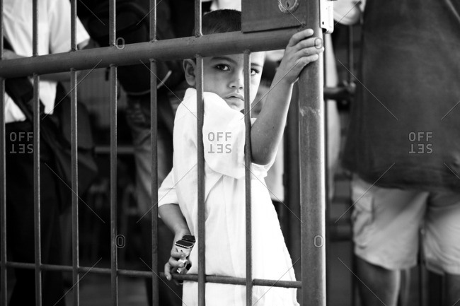 Managua, Nicaragua - April 30, 2009: Boy standing by a metal gate