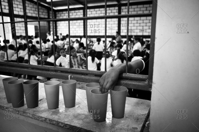 Managua, Nicaragua - April 30, 2009: Hand reaching for cup in a school lunch room