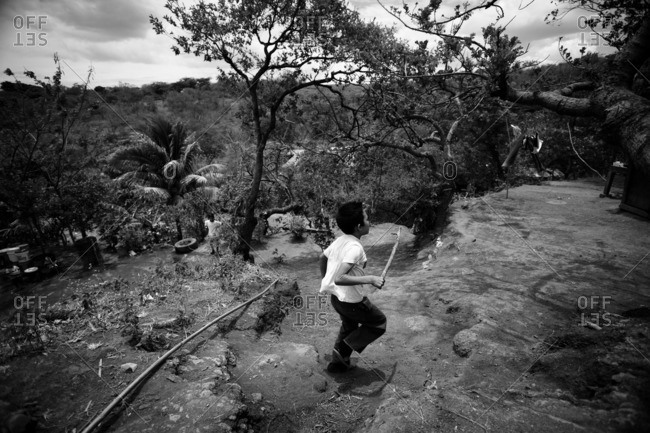 Managua, Nicaragua - April 30, 2009: Boys playing outside and running with a stick