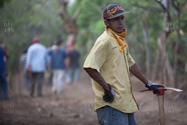 Managua, Nicaragua - April 30, 2009: Young man standing with pickaxe