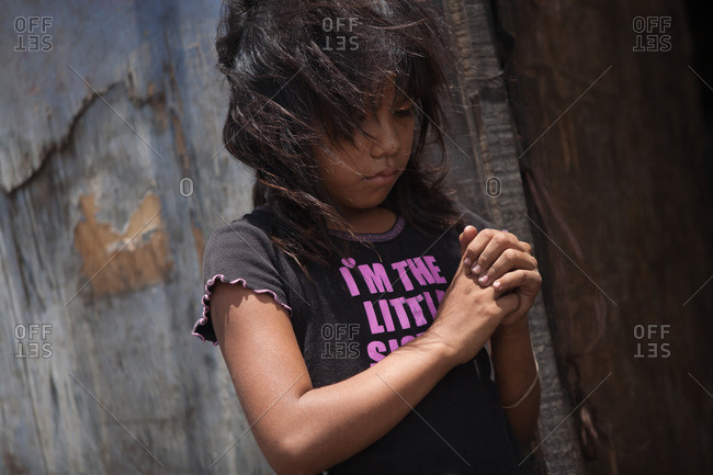 Managua, Nicaragua - May 1, 2009: Portrait of a little girl standing with hands together