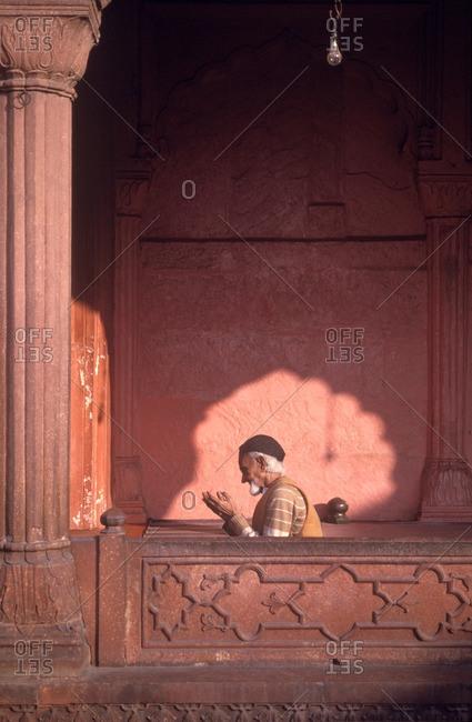 Old Delhi, India - March 23, 1994: Senior Muslim man praying in Jami Masjid Mosque